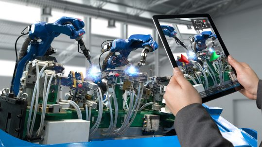 An engineer looking at a digital twin on a tablet with the machine in the background